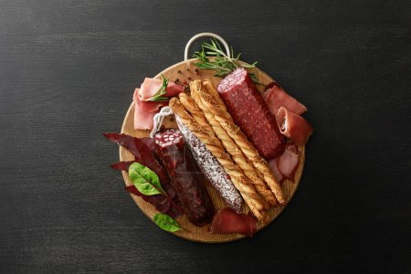 Photo for Top view of delicious meat platter served with breadsticks and herbs on board on wooden black table - Royalty Free Image