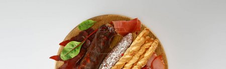 Photo for Top view of delicious meat platter served with breadsticks and herbs on board isolated on white, panoramic shot - Royalty Free Image