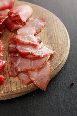 Photo pour Délicieux plateau de viande avec jambon sur planche de bois sur surface noire - image libre de droit