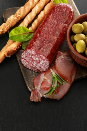 Photo for Delicious meat platter served with olives and grissini on board on black surface - Royalty Free Image