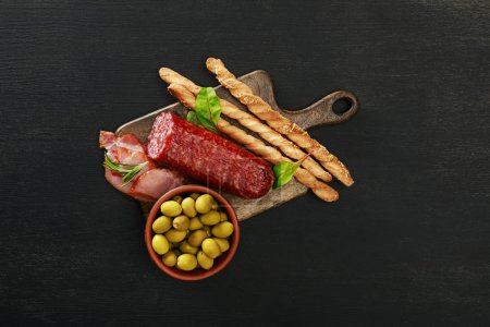 Photo for Top view of delicious meat platter served with olives and grissini on board on black surface - Royalty Free Image