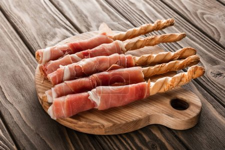 Photo for Delicious meat platter with grissini and prosciutto on wooden board - Royalty Free Image