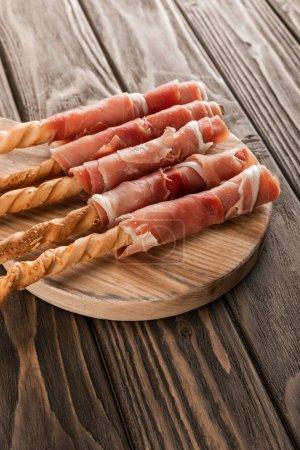 Photo pour Assiette à viande délicieuse avec grissini et prosciutto sur carton en bois - image libre de droit
