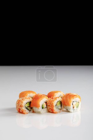 Photo for Delicious Philadelphia and California sushi with salmon and masago caviar on white surface isolated on black - Royalty Free Image