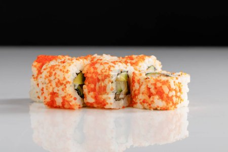 Photo for Delicious California roll with avocado, salmon and masago caviar on white surface isolated on black - Royalty Free Image