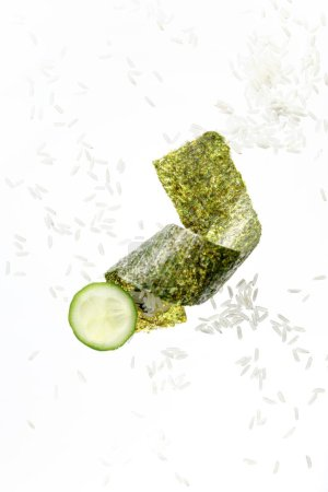 Photo for Top view of nori seaweed piece, cucumber slice and rice isolated on white - Royalty Free Image