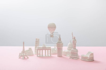 Photo pour Small figurines from different countries on grey and pink - image libre de droit