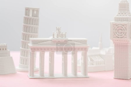 selective focus of brandenburg gate figurine near big ben tower statuette on grey and pink