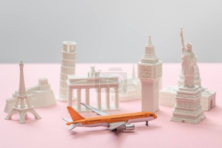 Photo pour Toy airplane near small statuettes of different countries on grey and pink - image libre de droit