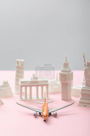 Photo pour Selective focus of toy airplane near small statuettes of different countries on grey and pink - image libre de droit