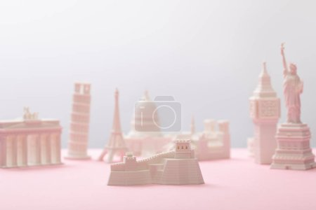 selective focus of great wall figurine near statuettes on grey and pink