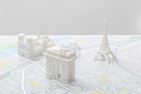 selective focus of small figurines on map of paris isolated on grey