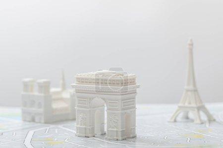 Photo pour Foyer sélectif de l'arc de triomphe près de petites figurines sur carte de paris isolé sur gris - image libre de droit