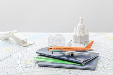Photo pour Foyer sélectif de jouet avion près de passeports et de petites figurines sur la carte de l'italie isolé sur gris - image libre de droit
