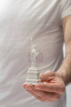 Photo pour Cropped view of man holding small statue of liberty - image libre de droit