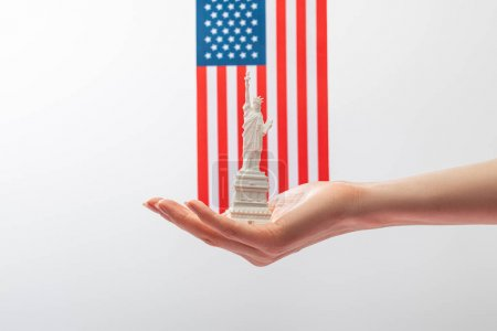 Photo pour Cropped view of woman holding small statue of liberty near american flag isolated on white - image libre de droit