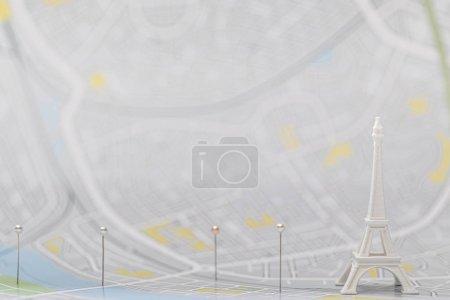 селективное фокусирование булавок рядом с маленькой фигуркой Эйфелевой башни на карте Парижа