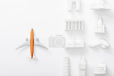 Photo pour Top view of toy plane near statuettes from different countries of europe isolated on white - image libre de droit