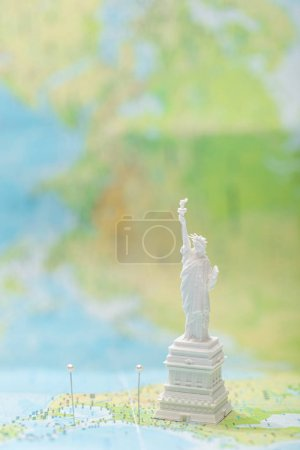 Photo pour Small statue of liberty on map of usa with pins - image libre de droit