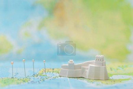Photo pour Petite figurine avec grand mur près des épingles sur la carte - image libre de droit