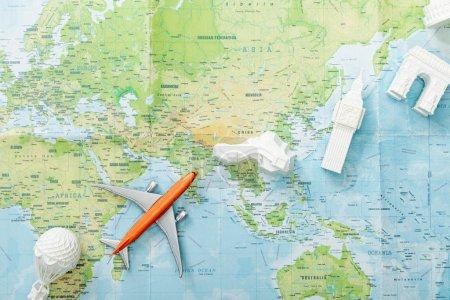 Photo pour Top vue d'un petit avion sur la carte près des attractions du monde - image libre de droit