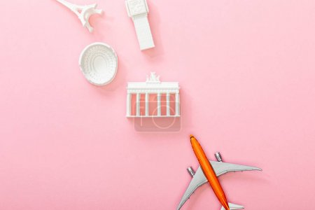 Photo pour Top view of toy plane near figurines with attractions on pink - image libre de droit
