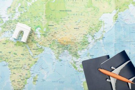 Photo pour Vue du dessus de l'avion jouet sur les passeports près de l'arc de triomphe figurine sur la carte - image libre de droit
