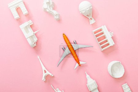 Photo pour Top view of figurines from countries near toy plane on pink - image libre de droit