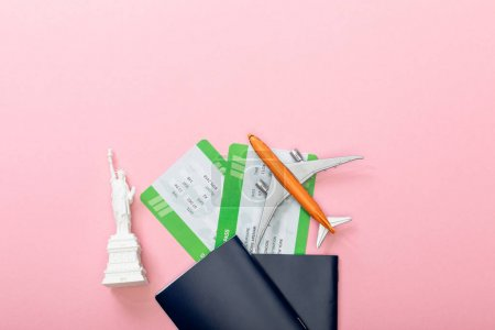 Photo pour Top view of air tickets near passports and small statue of liberty on pink - image libre de droit