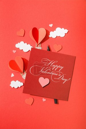 top view of paper heart shaped air balloons in clouds near card with happy valentines day lettering on red background