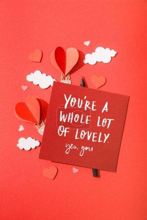 Photo pour Vue du dessus des ballons d'air en forme de coeur de papier dans les nuages près de la carte avec vous êtes beaucoup de belle oui, vous lettrage sur fond rouge - image libre de droit