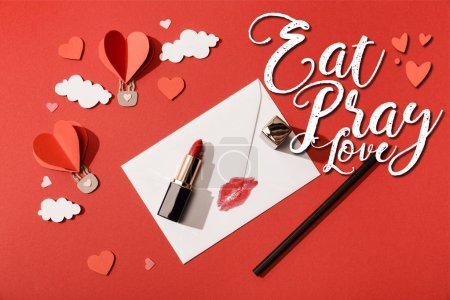 Photo pour Top view of paper clouds and heart shaped air balloons, lipstick and pencil near envelope with lip print and eat pray love lettering on red background - image libre de droit