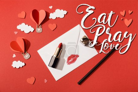 Photo pour Vue du dessus des nuages de papier et des ballons à air en forme de coeur, rouge à lèvres et crayon près de l'enveloppe avec impression sur les lèvres et manger prier l'amour lettrage sur fond rouge - image libre de droit