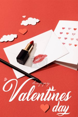 Photo for Paper clouds and hearts, lipstick, greeting card and envelope with lip print near happy valentines day lettering on red background - Royalty Free Image
