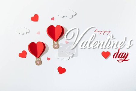 Photo for Top view of paper heart shaped air balloons in clouds near happy valentines day lettering on white background - Royalty Free Image