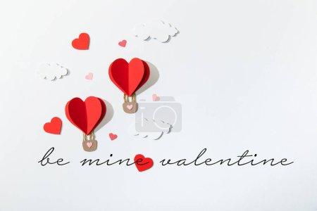 Photo pour Vue du haut des ballons d'air en forme de coeur de papier dans les nuages près de la mine lettrage de la Saint-Valentin sur fond blanc - image libre de droit