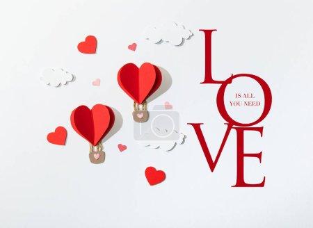 Photo pour Vue du dessus des ballons d'air en forme de coeur en papier dans les nuages près de l'amour est tout ce dont vous avez besoin lettrage sur fond blanc - image libre de droit
