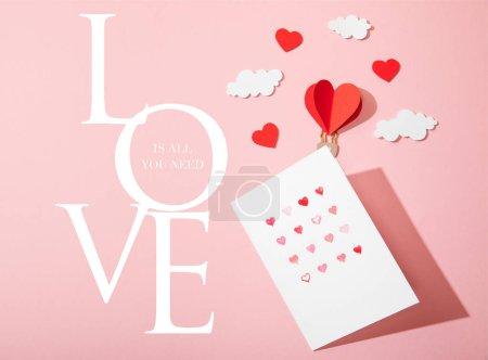 Photo pour Vue du haut de la carte de vœux avec des coeurs près du papier ballon à air en forme de coeur dans les nuages et l'amour est tout ce dont vous avez besoin lettrage sur rose - image libre de droit