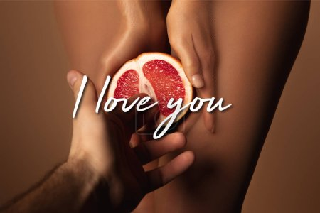 Photo for Cropped view of man reaching woman in nylon tights holding grapefruit half near i love you lettering on brown - Royalty Free Image