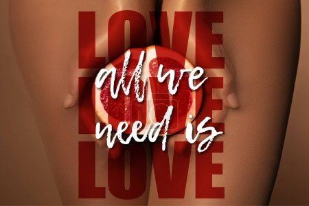 Photo pour Cropped view of woman in nylon tights holding grapefruit half near all we need is love lettering on brown - image libre de droit