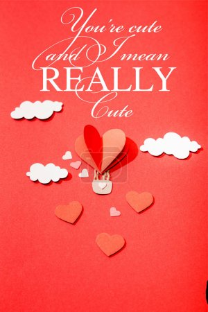 Photo for Top view of paper heart shaped air balloon in clouds near you're cute and i mean really cute lettering on red background - Royalty Free Image