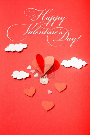 Photo for Top view of paper heart shaped air balloon in clouds near happy valentines day lettering on red background - Royalty Free Image