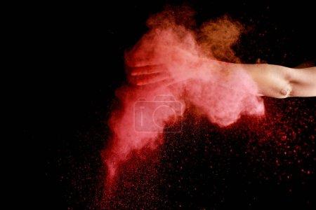 Photo pour Main féminine en rose coloré holi explosion de peinture sur fond noir - image libre de droit