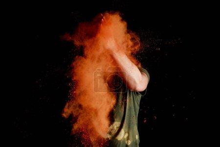 Photo pour Femme avec explosion de peinture holi orangée devant le visage sur fond noir - image libre de droit