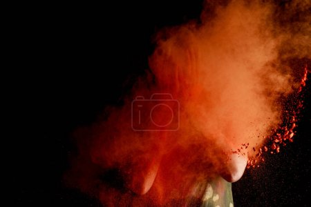 Photo for Woman with orange colorful holi paint explosion in front of face on black background - Royalty Free Image