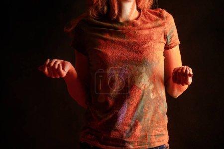 Photo pour Vue croisée d'une femme avec de la peinture holi orangée sur un t-shirt isolé sur noir - image libre de droit