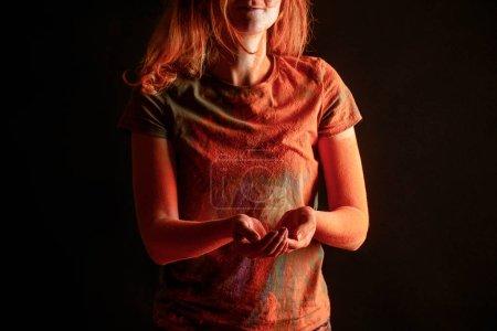 Foto de Vista cromada de la mujer con color naranja holi pintura en polvo aislado en negro. - Imagen libre de derechos
