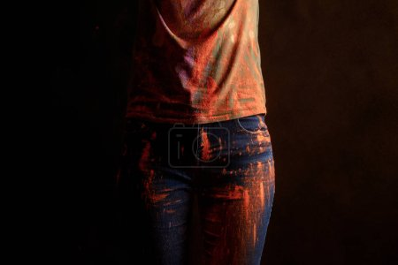 Photo for Cropped view of woman with orange colorful holi paint powder on clothes isolated on black - Royalty Free Image