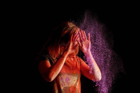 Photo pour Femme recouvrant le visage d'un nuage de peinture holi violette sur fond noir - image libre de droit