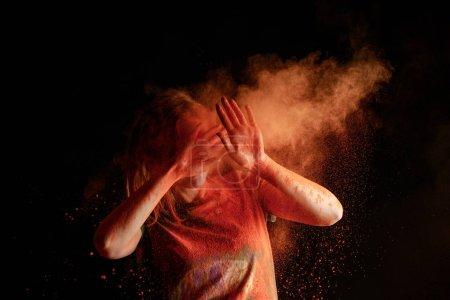 Photo pour Femme recouvrant le visage d'un nuage de couleur orange holi sur fond noir - image libre de droit